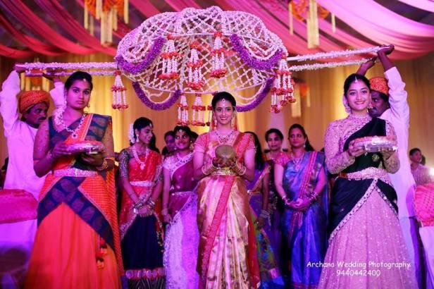 Bride walking under a unique phoolon ka chadar