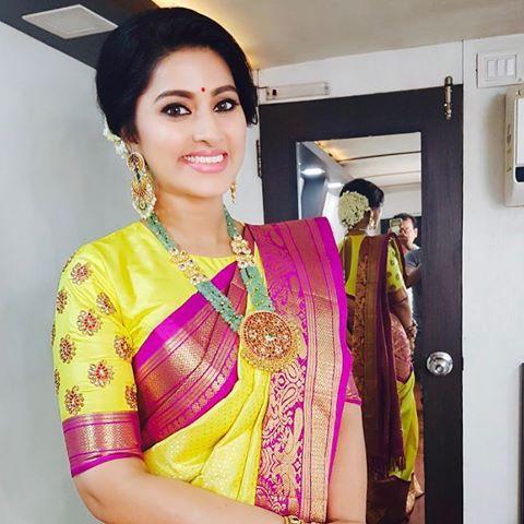 A bright yellow Kanjivaram and sneha all smiles